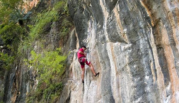 rock climber ascending the cliffs on Rai Leh Beach in Krabi Thai