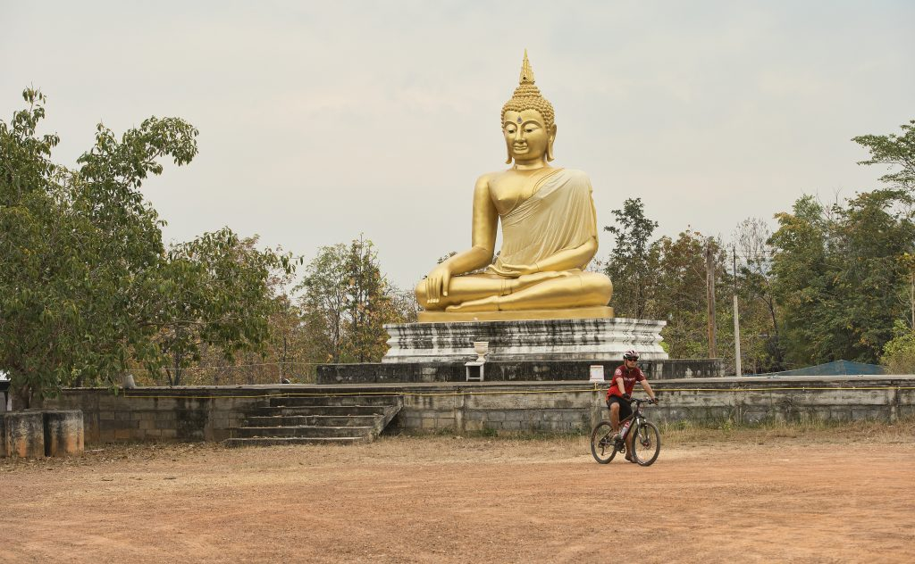 Cyclist and Buddha in rural Thailand